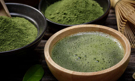 Japanese organic matcha green tea powder in bowl with wire whisk and green tea leaf on wooden background, Organic product from the nature for healthy with traditional style