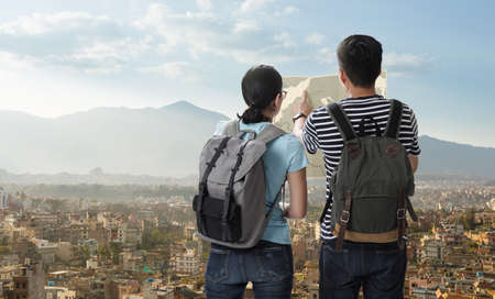 Travelers couple with the backpack on the top of mountain and look searching direction on location map, Adventure and travel in the concept, Travelling tour in Asia: Nepal Cities