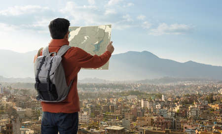A young traveler man on the top of mountain with backpack and look searching direction on location map, Adventure and travel in the concept, Travelling tour in Asia: Nepal Cities
