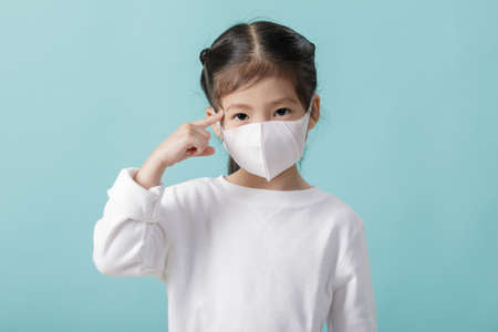 Asian little child girl is wearing medical face masks to protect themselves from pollution Coronavirus flu virus, New coronavirus 2019-nCoV  , Empty space isolated on blue background