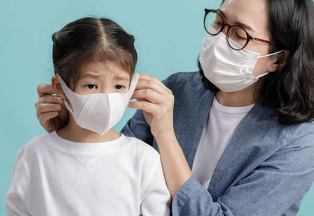 Mom and Asian little child girl is wearing medical face masks to protect themselves from pollution Coronavirus flu virus, New coronavirus 2019-nCoV  , Empty space isolated on blue background