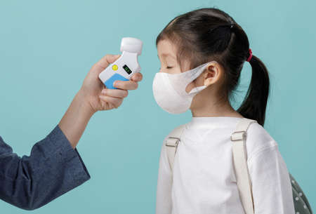 Mom and Asian little child girl wearing respirator mask to protect coronavirus outbreak and body temperature checked amid, New virus Covid-19   concept, isolated on blue background