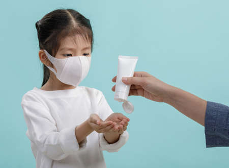 Mom and Asian little child girl wearing respirator mask to protect coronavirus outbreak and washing hands with alcohol gel, New virus Covid-19   concept, isolated on blue background 免版税图像