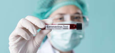 Doctor wearing respirator mask for stop Coronavirus Outbreak (COVID-19) and holding testing patients blood samples for Corona Virus   in Laboratory, Empty space isolated on long banner