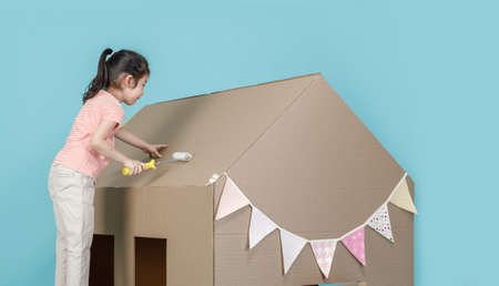Asian little child girl painting her cardboard house isolated on blue long banner, Creative at home with family concept 免版税图像
