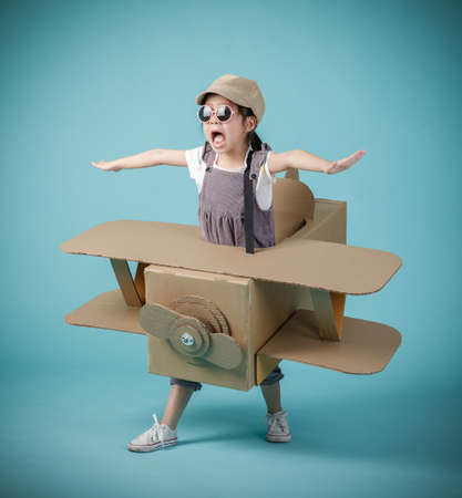 Asian little child girl playing with cardboard toy airplane handicraft isolated on blue background, Creative at home and dreams of flight concept