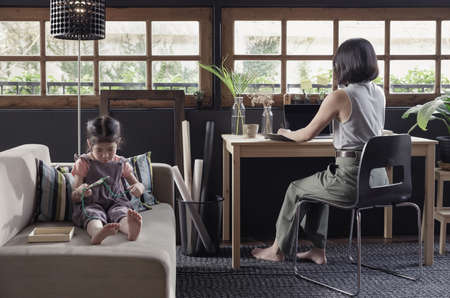 Working from home lifestyle mom using smartphone on the desk and her child girl learning the toy on sofa in the living room, Quarantine isolation during the Coronavirus (COVID-19) health crisis