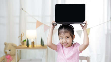 Asian little child girl learning at home with laptop computer using meeting online app, Quarantine isolation during the Coronavirus (COVID-19) health care, online education concept 免版税图像