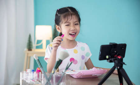 Happy little Asian girl beauty blogger recording video for teaching to use cosmetic make up.
