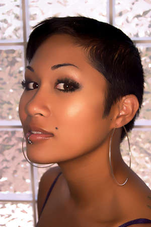 Headshot of pretty Asian glamour model with lip piercing photo