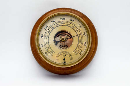 Barometro aneroide in una cassa di legno su sfondo bianco.