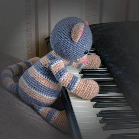 Amigurumi doll plays a musical instrument on sheet music.
