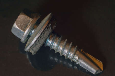 Roofing self-tapping screw with a drill  on a black  background close-up. 版權商用圖片