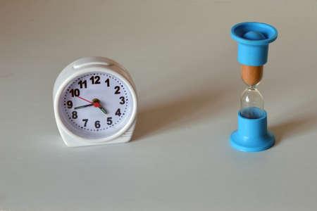 Alarm clock with arrows next to the hourglass. Фото со стока