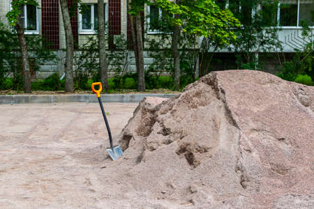 The shovel is stuck in a pile of sand.