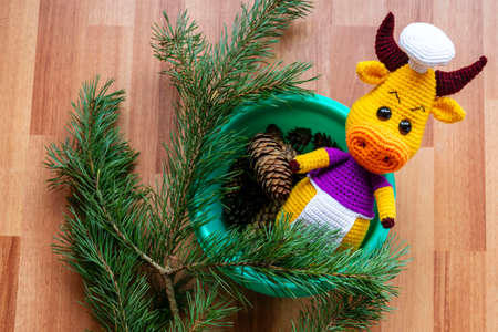 Doll amigurumi goby on the background of pine branches. Symbol 2021. Stockfoto