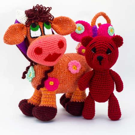 Amigurumi dolls a cow burgundy teddy bear are walking.