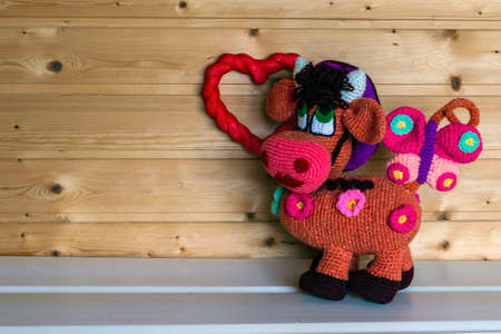 Handmade amigurumi dolls are photographed against the background of a wall of boards. Stockfoto