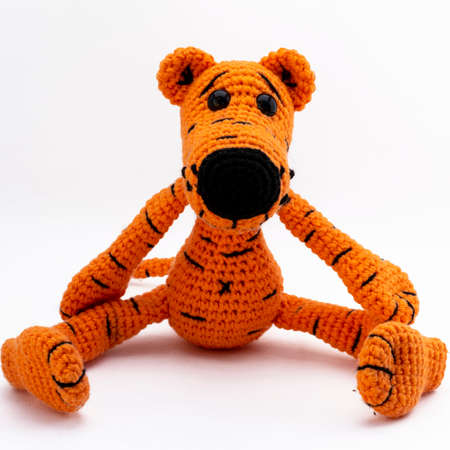 Amigurumi doll tiger poses for a photographer. White background, isolate.