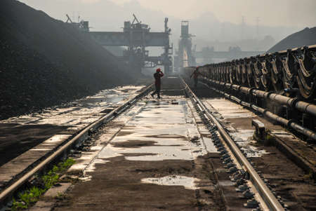 conveyor rail: the workers do their job near coal stockpile, Mae Moh mine, Lampang, Thailand