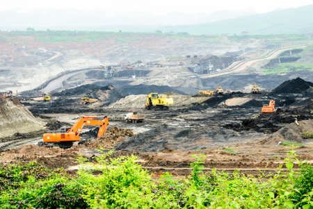 The backhoes and the bulldozer excavates lignite in the coal mine, Mae Moh mine, Lampang, Thailand  photo