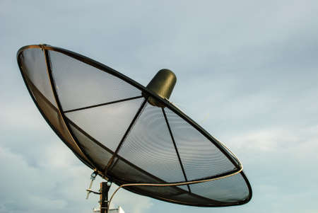 The black satellite dish with cloudy sky photo