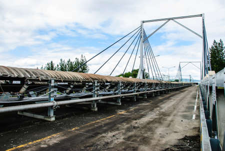conveyor rail: Coal was transported by coveyor belts from open-pit mine to the stock pile  Conveyor bridge was used when conveyor belts cross a road, Mae Moh mine, Lampang, Thailand