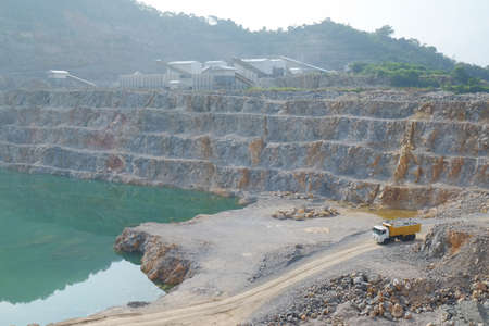 berm: A full-load of limestone is carrying out  by the mining truck and taken to the limestone processing plant.