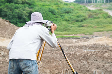 optical equipment: Builder surveyor working with optical equipment level at construction site.