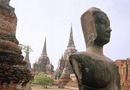 half headed buddha contemplates the ruins of ayutthya the ruined capital of thailand photo