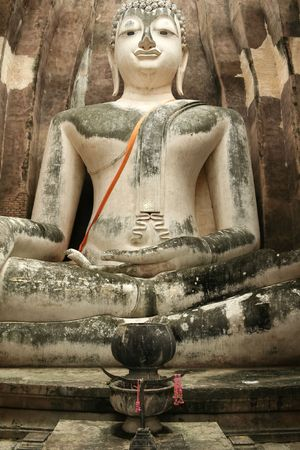 giant seated buddha amidst the ruins of an ancient temple in sukothai, northern thailand photo