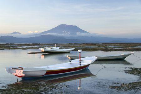 towering: peque�as embarcaciones en los arrecifes de nusa lembongan isla indonesia con balis gunung agung, volc�n, towering en segundo plano