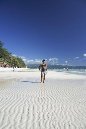 filipina girl in baeball hat and sunglasses on the white sand of boracay island in the philippines photo