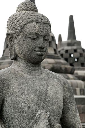 borobudur: stone buddha in front of stupas atop the  borobudur ruins near yogyakarta in java indonesia