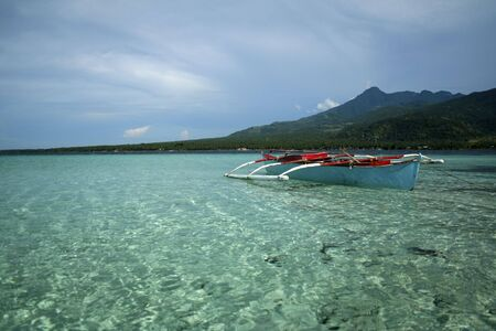 clear waters: traditional banka outrigger boat in clear waters of camiguin island in the philippines