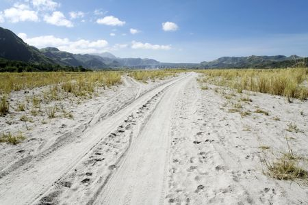 tyre tracks in sand running through crow valley leading to mount pinatubo in pampanga, luzon, the philippines photo
