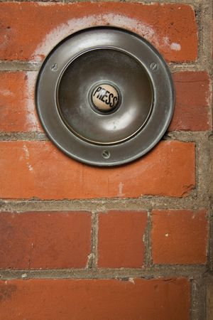 large old fashioned doorbell mounted on brick wall with button marked press