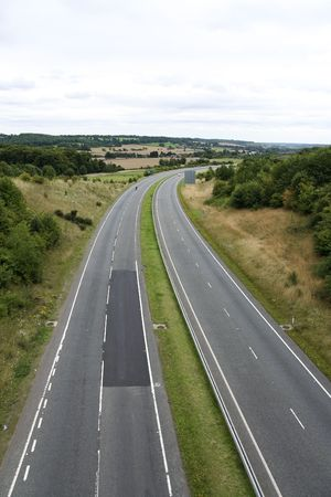 the carriageway: empty dual carriageway curving through the hertfordshire countryside in england