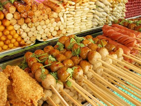hot dogs, fried chicken, fish and pork balls with sweet spicy sauce for sale at street market in bangkok thailand photo