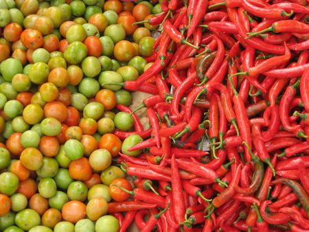 chillies and tomatoes arranged for sale at fresh food market in kota kinabalu, sabah, borneo photo