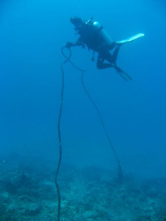 scuba diver lifting heavy anchor line in boracay the philippines photo
