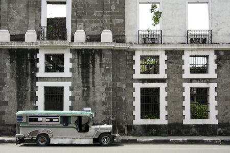 tradiional jeepney public transportation parked outside derelict building in intramuros manila, the philippines photo