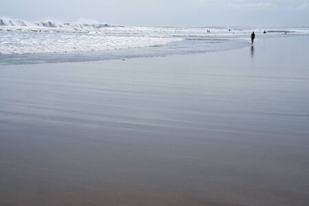 woman silhouetted walking on kuta beach bali at low tide photo