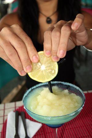 woman squeezing lemon into a frozen margarita photo