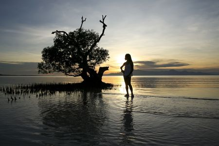 filipina: asian girl in mangroves backlit by sun setting over the volcanos of negros island in the philippines