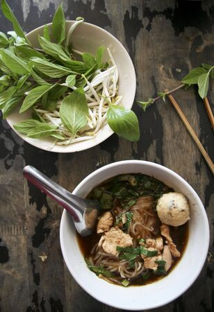 bowl of pungent thai pork noodle soup served with fresh sweet basil and beansprouts photo