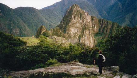inca architecture: woman tourist hiking the inca trail overlooking ruined incan city of machu picchu near cusco in peru south america
