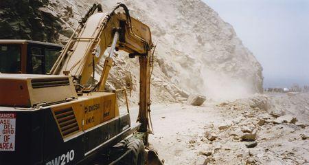 rockslide: digger clearing landslide on the pan-american highway in northern peru Editorial
