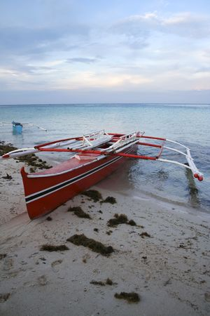 outrigger: outrigger banka boats at sunset on camiguin island, mindanao, the philippines