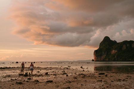 couple walk through rocks deposited by tsunami on koh phi phi thailand photo
